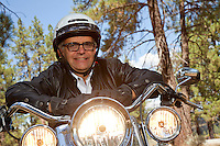 Senior man wearing helmet leaning on motorcycle handlebars in forest