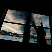 Jade Goodrich stands against her parents' bedroom window dressed from skiing wanting to go back out into the mountains surrounding Jackson, Wyoming.