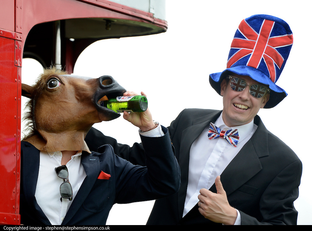 © Licensed to London News Pictures. 01/06/2012. Epsom , UK David Goddard (right) and Robin Voogd hang off the back of a bus wearing a horse mask and union flag outfit. Ladies Day today 1st June 2012 at Epsom 2012 Investic Derby Festival. The Queen will attend tomorrow's race meet as part of the 60th Jubilee celebrations. Photo credit : Stephen Simpson/LNP