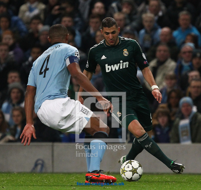 Picture by John  Rainford/Focus Images Ltd +44 7506 538356.21/11/2012.Vincent Kompany of Manchester City and Karim Benzema of Real Madrid during the UEFA Champions League match at the Etihad Stadium, Manchester.