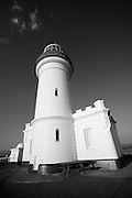 The lighthouse stands tall on the headland overlooking the Pacific Ocean