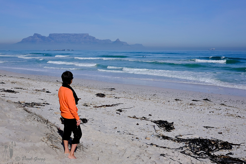 Table Mountain,Cape Town, South Africa. A tourist watches surfers enjoy an early morning wave at Bloubergstrand. Mussel and other shells litter the beach after heavy seas. A blanket of smog covers the base of Table Mountain in the early winter morning.