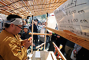 "A sells pallus-shaped lollipops at a stall during the Kanamara ""Penis"" Festival in Kawasaki, Japan. Kanamara means metal phallus, so named after a story dating back hundreds of years in which a local blacksmith made an iron phallus to protect a girl who was thought to be curse. Today, the festival participants are largely prostitutes STDs."