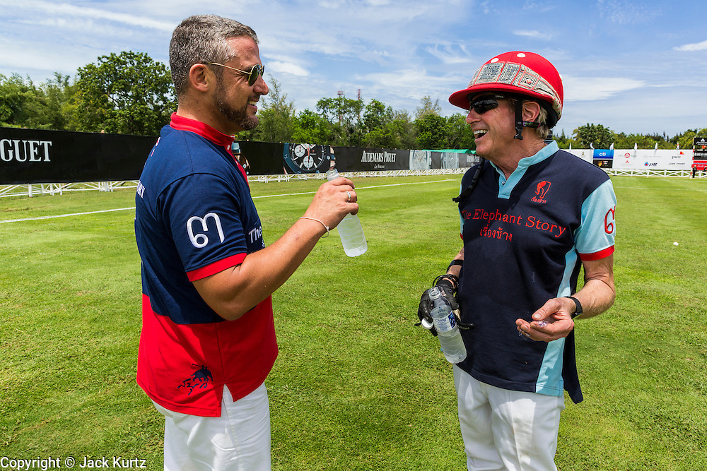 "28 AUGUST 2013 - HUA HIN, PRACHUAP KHIRI KHAN, THAILAND: JASON FRIEDMAN (left) and ED STORY chat at the King's Cup Elephant Polo Tournament in Hua Hin, Thailand. The tournament's primary sponsor in Anantara Resorts and the tournament is hosted by Anantara Hua Hin. This is the 12th year for the King's Cup Elephant Polo Tournament. The sport of elephant polo started in Nepal in 1982. Proceeds from the King's Cup tournament goes to help rehabilitate elephants rescued from abuse. Each team has three players and three elephants. Matches take place on a pitch (field) 80 meters by 48 meters using standard polo balls. The game is divided into two 7 minute ""chukkas"" or halves. There are 16 teams in this year's tournament, including one team of transgendered ""ladyboys.""     PHOTO BY JACK KURTZ"