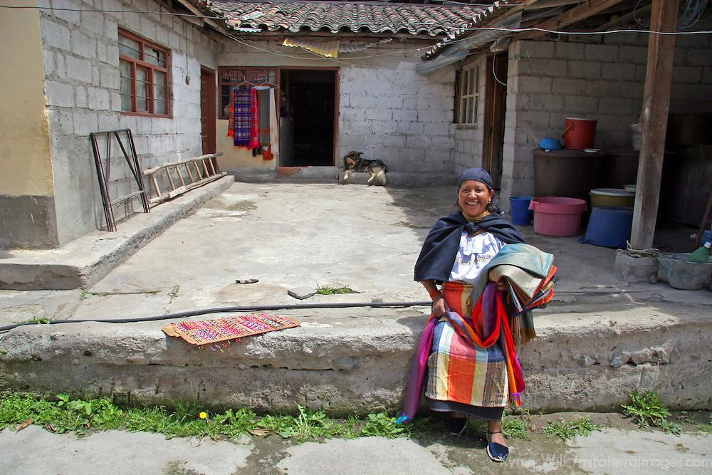 South America, Ecuador, Peguche. An Ecuadorian woman welcomes visitors to see her home in Peguche.