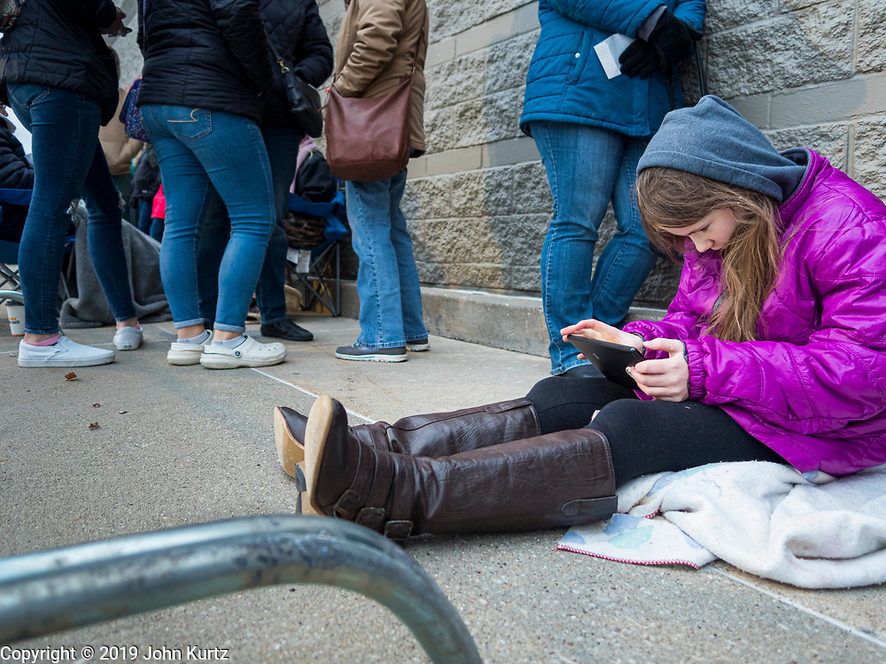 """28 NOVEMBER 2019 - ANKENY, IOWA: A girl in line at the Target store in Ankeny, Iowa, plays on her iPad while she, and others, wait for the store to open. """"Black Friday"""" is the unofficial start of the Christmas holiday shopping season and has traditionally thought to be one of the busiest shopping days of the year. Brick and mortar retailers, like Target, are facing increased pressure from online retailers this year. Many retailers have started opening on Thanksgiving Day. Target stores across the country opened at 5PM on Thanksgiving to attract shoppers with early """"Black Friday"""" specials.     PHOTO BY JACK KURTZ"""