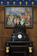 Clock and painting, c. 1925, by Jeanne Thil, 1887-1968, of Philippa de Hainaut pleading with her husband Edward II to pardon the Burghers of Calais, in the Smoking Room, in the Chateau de Hardelot, originally the site of a 12th century castle, rebuilt over the centuries and finally redeveloped in the 19th century, in Condette, Pas-de-Calais, France. The current building dates from 1865-72, when its owner, Henry Guy, rebuilt the chateau in Neo-Tudor style. Since 2009 the building has housed the Centre Culturel de l'Entente Cordiale, with an arts programme involving France and Britain. It is situated within the Reserve Naturelle Regionale du Marais de Condette, a protected marshland area. Picture by Manuel Cohen