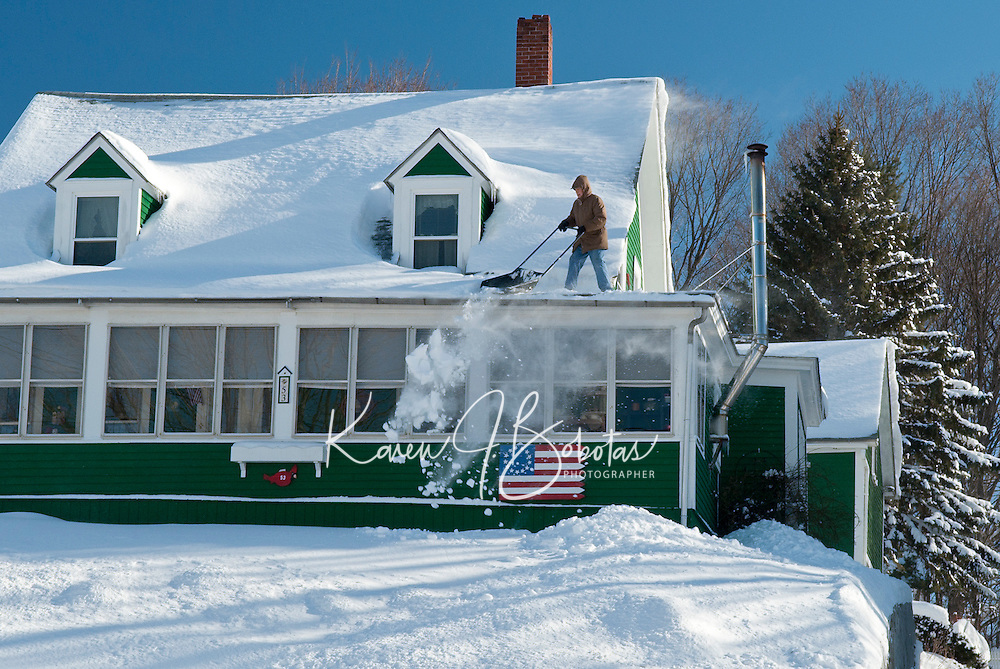 The skies have cleared but for many Laconia residents the work continues removing snow that fell during Wednesday's storm.  (Karen Bobotas/for the Laconia Daily Sun)