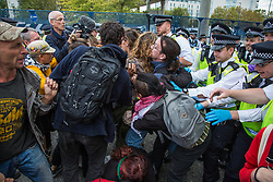 London, UK. 7 September, 2019. Metropolitan Police officers attempt to force back activists blocking the road in front of a truck attempting to deliver to ExCel London during the sixth day of Stop The Arms Fair protests against DSEI, the world's largest arms fair. The sixth day of protests was billed as a Festival of Resistance and included performances, entertainment for children and workshops as well as activities intended to disrupt deliveries to ExCel London for the arms fair.
