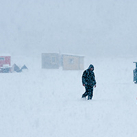 Ice Fishing during a snow storm on Lake Winnipesaukee. A fisherman checks his tip ups.  <br /> <br /> All Content is Copyright of Kathie Fife Photography. Downloading, copying and using images without permission is a violation of Copyright.