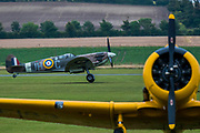 18 Spitfires take off, behind other classic planes such as this yellow Harvard, from the grass airstrip for the final flypast - The Duxford Battle of Britain Air Show is a finale to the centenary of the Royal Air Force (RAF) with a celebration of 100 years of RAF history and a vision of its innovative future capability.