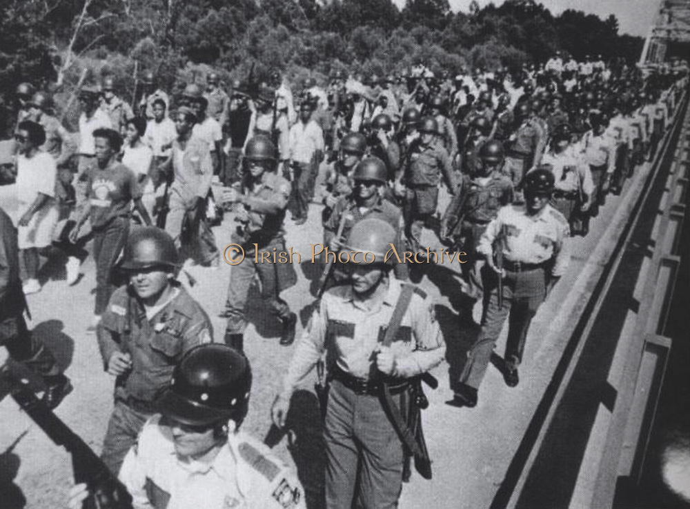 FLORIDA PARISHES CIVIL RIGHTS STRUGGLE, USA:  National guardsmen and state troopers shield black marchers from onlookers near Denham Springs during their 1967 trek from Bogalusa to Baton Rouge. More than 800 National Guardsmen were ordered by Louisiana Governor John McKeithen to provide additional protection.