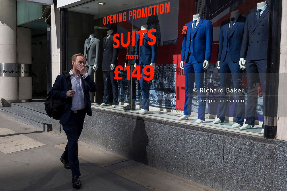 City workers walk past a new menswear retailer in the Square Mile, selling suits from £149, on 3rd March 2017, in the City of London, England.