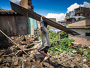 03 AUGUST 2015 - SANKHU, NEPAL:  A laborer hauls corrugated metal used as roofing to a work site where he will rebuild a home destroyed in the earthquake in Sankhu, a community about 90 minutes from central Kathmandu. The home was damaged in the earthquake and the owners hope to rebuild on the site but first half to take down what's left of the existing home. The Nepal Earthquake on April 25, 2015, (also known as the Gorkha earthquake) killed more than 9,000 people and injured more than 23,000. It had a magnitude of 7.8. The epicenter was east of the district of Lamjung, and its hypocenter was at a depth of approximately 15km (9.3mi). It was the worst natural disaster to strike Nepal since the 1934 Nepal–Bihar earthquake. The earthquake triggered an avalanche on Mount Everest, killing at least 19. The earthquake also set off an avalanche in the Langtang valley, where 250 people were reported missing. Hundreds of thousands of people were made homeless with entire villages flattened across many districts of the country. Centuries-old buildings were destroyed at UNESCO World Heritage sites in the Kathmandu Valley, including some at the Kathmandu Durbar Square, the Patan Durbar Squar, the Bhaktapur Durbar Square, the Changu Narayan Temple and the Swayambhunath Stupa. Geophysicists and other experts had warned for decades that Nepal was vulnerable to a deadly earthquake, particularly because of its geology, urbanization, and architecture.    PHOTO BY JACK KURTZ