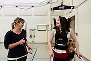 Riley Ljungdahl, 12, of Longmont, talks with Intern Aly Clark, left, while working on her physical therapy with Clinical Exercise Specialist Emma Dawson, right, Tuesday, April 30, 2013, at the Peak Center at Craig Hospital. Ljundhal travels to Englewood from Longmont twice a week for PT.<br /> (Matthew Jonas/Times-Call)