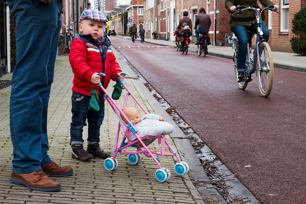 Nederland, Tilburg, 18 jan 2014<br /> Kleine jongen met pet en kinderwagen wacht met z'n vader tot ze over kunnen steken. <br /> <br />  Foto: Michiel Wijnbergh