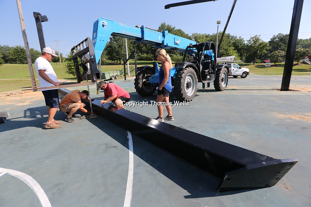 David Singleton, from left, Anthony Lee, David Gilbert and his daughter, Kimberly all from Wilco Services get ready to install of of the last main support beams for the new canopy to cover the basketball courst at Gumtree Park