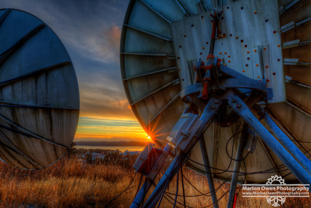 A low, morning sun peeks around a satellite dish near Kodiak, Alaska.