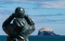 View of sculpture called The Watcher by Kenny Hunter and Bass Rock in Firth of Forth from North Berwick, East Lothian, Scotland, UK