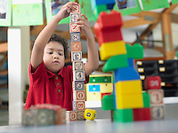 Boy playing with alphabet blocks in classroom