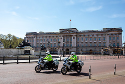© Licensed to London News Pictures. 14/04/2020. London, UK. Two police outriders patrol a deserted Buckingham Palace as the majority of people continue to stay away from the Capital during lockdown as one in five deaths are now linked to Covid-19 and Foreign Secretary, Dominic Raab announced yesterday that lockdown could last another month. Photo credit: Alex Lentati/LNP