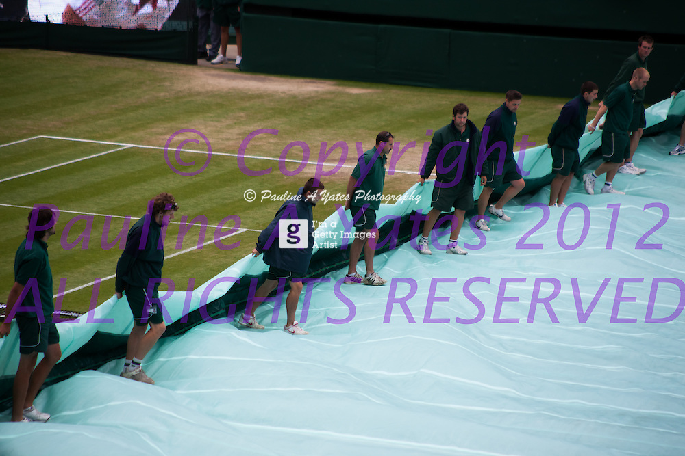Rain briefly stopped play at Wimbledon, but the ground staff swiftly removed the rain covers so play can continue