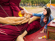 08 JANUARY 2015 - BANGKOK, THAILAND: A woman touches a ball of amber held by a statue of a revered Buddhist monk while she meditates. Buddhist in Bangkok have a chance to meditate in front of seven large statues of revered Buddhist monks and worship a hair relic of the Buddha at a series of altars on Sanam Luang near the Grand Palace in Bangkok.    PHOTO BY JACK KURTZ