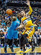 Charlotte Hornets guard Kemba Walker (15) drives around Denver Nuggets center Jusuf Nurkic (23) during the first half of an NBA basketball game in Charlotte, N.C., Saturday, March 19, 2016. (AP Photo/Mike McCarn)