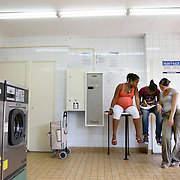 """Nederland Rotterdam 01-06-2009 20090601 Foto: David Rozing            ..Achterstandswijk Pendrecht Rotterdam zuid. Meiden, 1 van hen 9 maanden zwanger,  doen de was in washoken helpen een meisje dat haar huiswerk maakt  in de openbare wasserette. Beperkte liquide middelen, huishoudboekje, kosten huishouding, besparen, leasen., huren, armzalig, krap bij kas zitten,  Girls washing clothes om deprived area / projects """"Katendrecht """" This area is on a list with projects which need help of the government because of degradation in the area etc., project, suburb, suburbian, problem. Neighboorhood, neighboorhoods, district, city, problems,  daily life Holland, The Netherlands, dutch, Pays Bas, Europe ..Foto: David Rozing"""