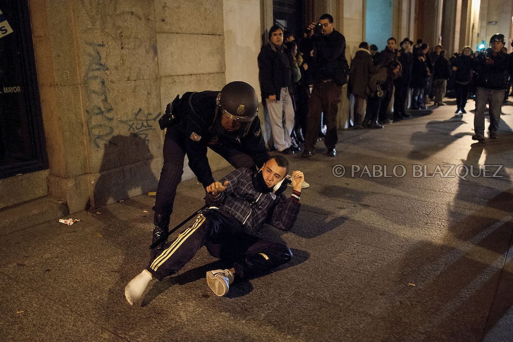 A riot policeman arrest a protester during clashes after the 'Surrounding the Congress' demonstration at Atocha Street on December 14, 2013 in Madrid, Spain. Social movements groups called a 'Rodea el Congreso' 'Surrounding the Parliament' protest in reaction to the financial and social cuts, but also a new law the Spanish government is working that aims to set heavy fines. Around 1,500 policemen were on duty to protect the congress. The bill will set up fines of up to 30,000 euros for offenses related to social movements protests, insulting the state or offending or filming the authorities. After the demonstration some protesters clashed with riot policemen