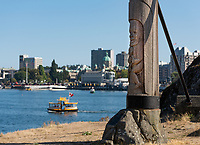 Poles carved by the Songhees First Nation in Victoria, BC, overlook the Inner Harbour with ferries and the Legislature Buildings.