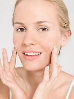 Young Woman Applying Facial Cream portrait close up