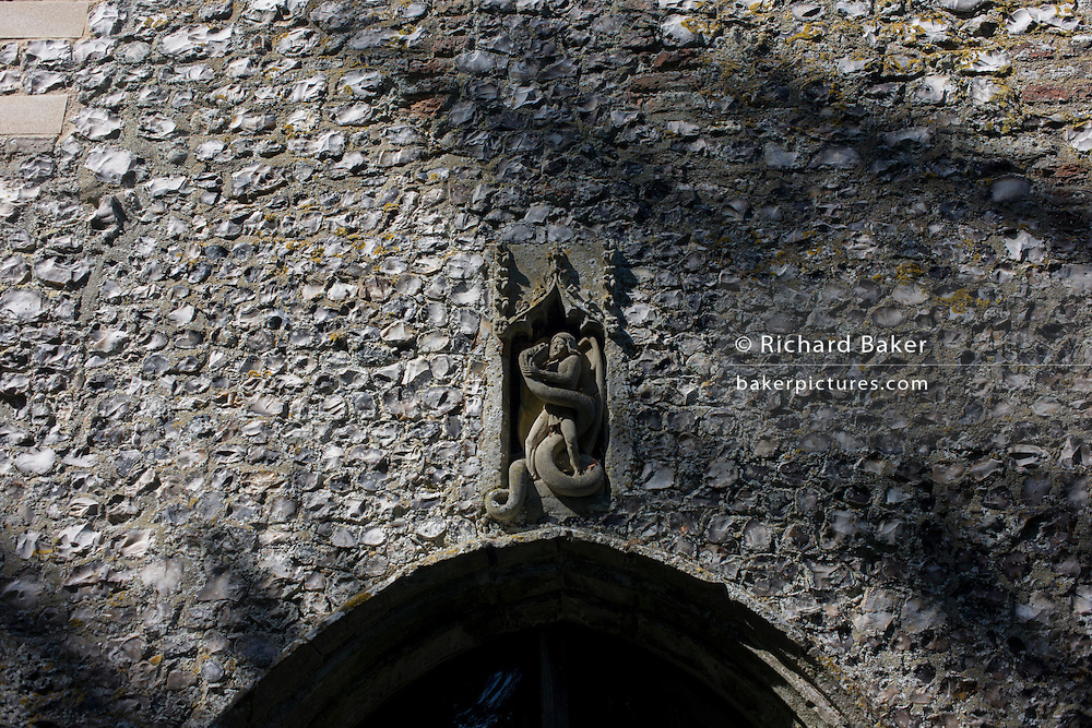 Flint wall architecture and carvings of St Michael's Anglican church at Irstead, on the Norfolk Broads.
