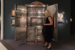 "© Licensed to London News Pictures. 29/06/2017. London, UK.  A staff member presents ""An Exclusive Jubilee Fire Resistant Safe"", 1869, by F. Wertheim & Co.  Members of the public visit Masterpiece London, a leading art fair held in the grounds of the Royal Hospital Chelsea.  The fair brings together 150 international exhibitors presenting works from antiquity to the present day and runs 29 June to 5 July 2017.  Photo credit : Stephen Chung/LNP"