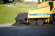 tarmac being laid by road construction equipment in Auckland, New Zealand