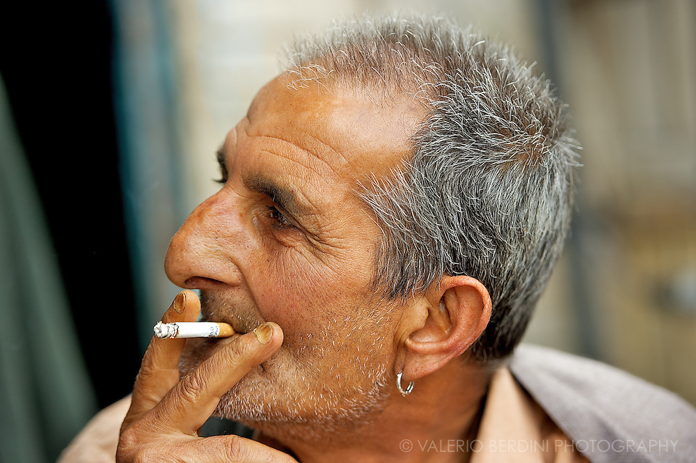 A puff at a western cigarette and a earring. Quite an unusual view on the muslim city of Srinagar. Kashmir. India