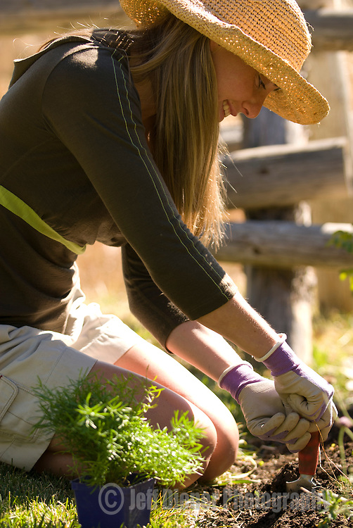 A young woman smiles while gardening in Jackson Hole, Wyoming.