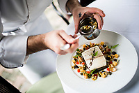 The chef puts the final touches on a seabass dish at Le Beaulieu restaurant at the Metropole hotel.