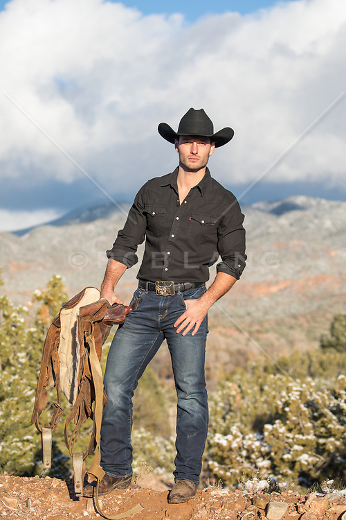 All American cowboy outdoors with a saddle Hot cowboy holding a saddle on a mountain range