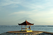 Lone figure in beachside pagoda, with Bali's sacred mountain, Gunung Agung, in background, viewed from Sanur Beach at sunrise. Sanur, Bali, Indonesia.