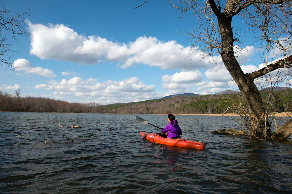 Woman kayaking in spring on flooded farm fields in The Pomainville Wildlife Management Area along Otter Creek in Pittsford, Vermont.