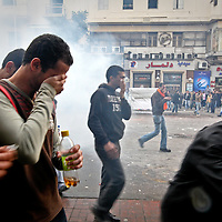 Demonstrators flee as tear gas covers a street during battles with riot police in downtown Cairo, Egypt. January 2011.