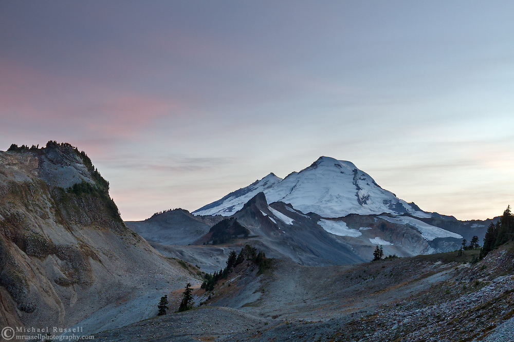Sunset over Happy Bunny Butte, Coleman Pinnacle and Mount Baker (L to R) in early Fall.  The 2014/2015 winter had very little snow, so there is likely less snow/ice here than a typical October day. Photographed while hiking the Chain Lakes Trail (on side of Table Mountain) in the Mount Baker Wilderness, Washington State, USA.