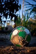 Bolivia.  An old, beat up soccer ball on the dirt floor of a families yard.