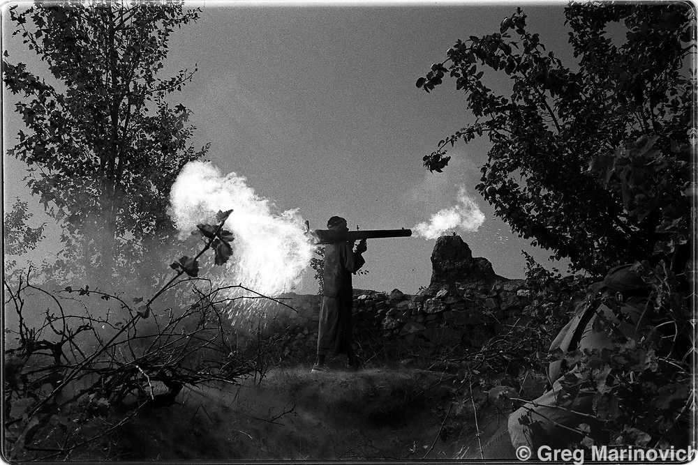 An Afghan mujehadin fighting with the Northern Alliance fires at Taliban positions Sept 1999 near Charikar on the Shomali plains.  (Greg Marinovich)