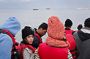 Turkey, Izmir, Cesme,<br /> <br /> A refugee girl is waiting to get on the boat with other refugees, as already an other boat is on the way to Chios, as seen in the background.<br /> January 2016 refugees from Afghanistan, Iran, Syria are ready for leaving Turkey to Greece hoping to reach the Greek Aegean islands Chios. Which is just a few nautical miles (6-8) away. The majority of the refugees came from war torn countries such as Syria and Afghanistan.<br /> A rubber boat is filled up with up to 60 people, men, women, children and babies.<br /> The henchman of the smugglers put as many as he can into the boat. The refugees had to be quick in entering the boat on a wild beach, with stone and rocks. Some other guys helping the henchman to prepare the boat and help them to organize the loading. Parents carry their kids to the boat. Its not a aloud to put on big luggage on the boat, only a small backpack or a bag. <br /> More than fourty-five thousand  refugees got from this beach here to Chios, over last 6 month.<br /> <br /> keine Veroeffentlichung unter 50 Euro*** Bitte auf moegliche weitere Vermerke achten***Maximale Online-Nutzungsdauer: 12 Monate !!