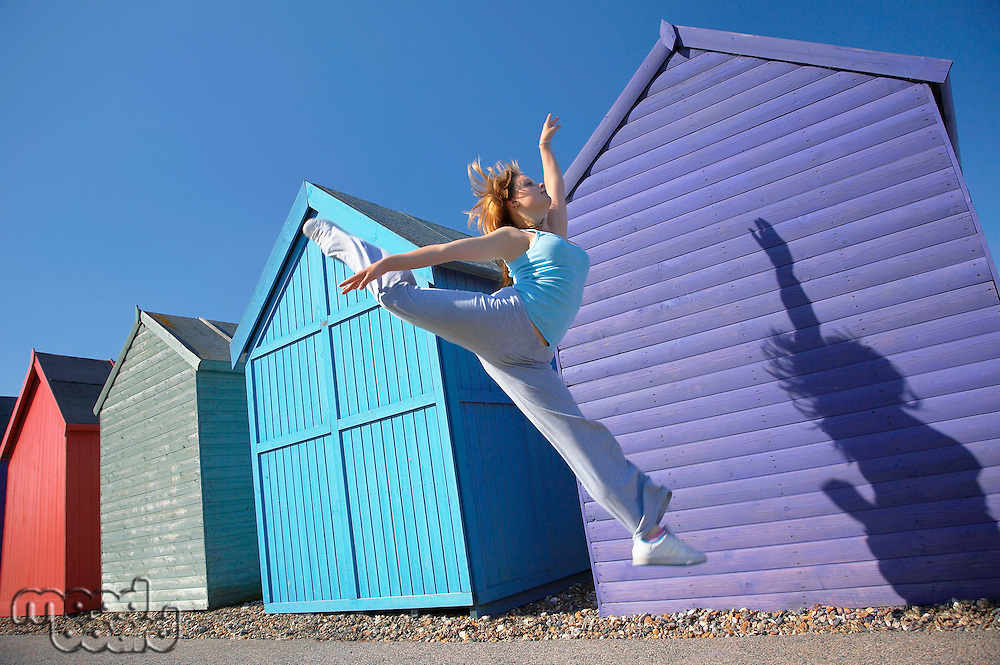 Woman jumping in front of beach huts