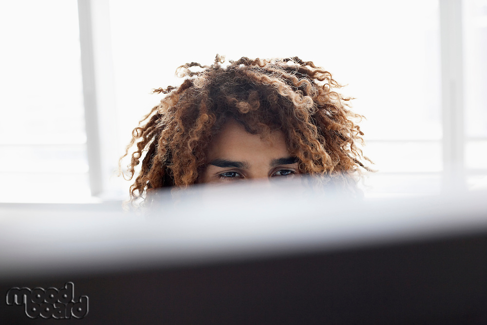 Young man using computer sitting at desk close up