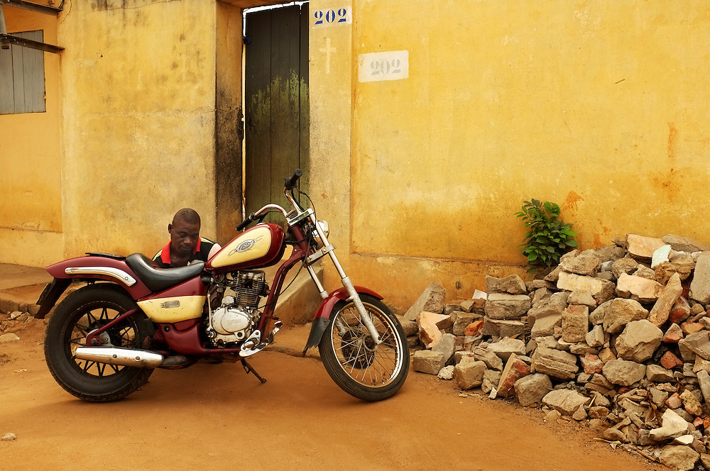 LOME, TOGO -  13-01-29 - A former fuel smuggler, who left because of increasing threats to his personal safety, washes a motorcycle belonging to his former boss, who manages several fuel smuggling depots. Photo by Daniel Hayduk