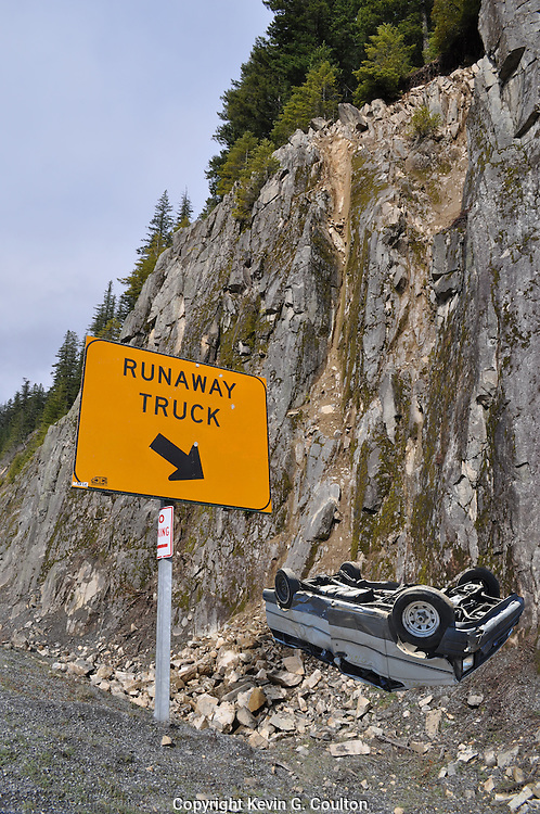 Humorous photograph of a RUNAWAY TRUCK RAMP sign changed to read RUNAWAY TRUCK with the arrow lowered to point at a wrecked truck at the base of a cliff.